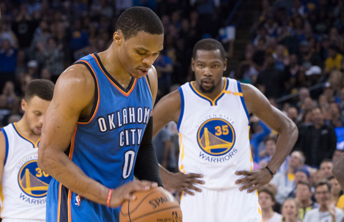 Kevin Durant looks on as Russell Westbrook shoots a free throw.