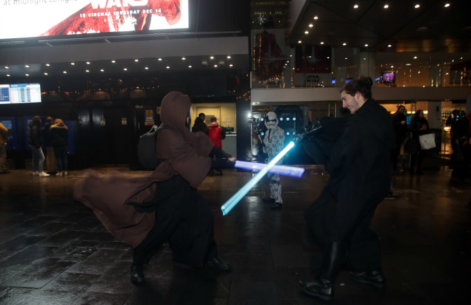 Fans in costume duel with lightsabers
