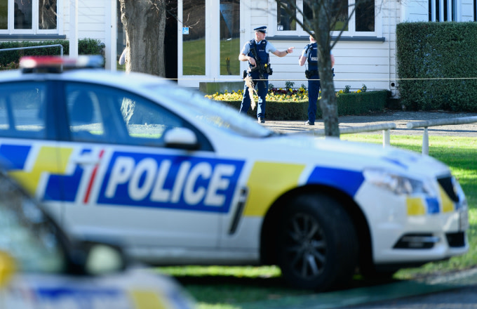 Armed police officers are seen at Riccarton Racecourse