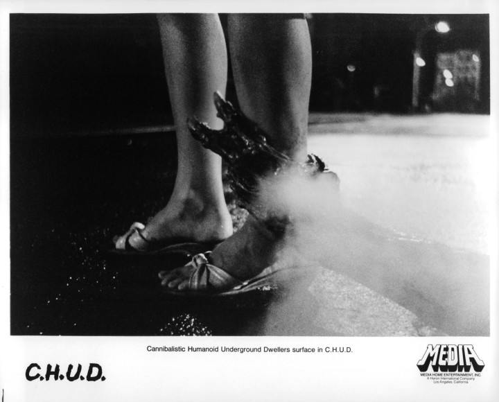 A still from CHUD, featuring a monster reaching for a woman's sandaled ankle
