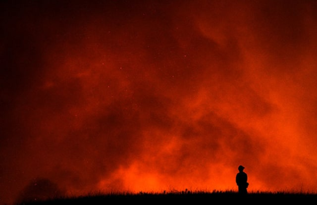 A firefighter watches as a California wildfire rages.