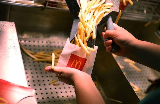 A  McDonald's crew member preparing fries.