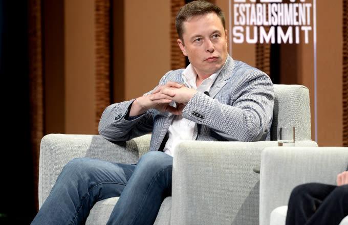 Elon Musk sits on a panel.