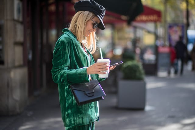 Gitta Banko with a Starbucks coffee to go and a phone texting