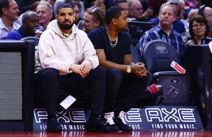 Drake sitting at a Toronto Raptors game.