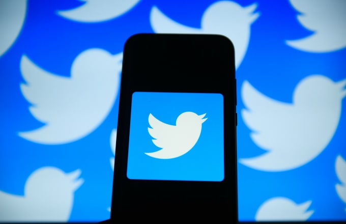 Twitter logo is seen on an android mobile phone in front of a computer screen