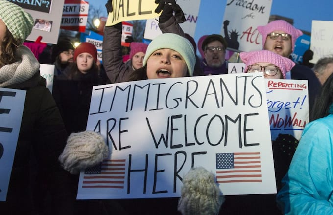 Woman holding 'Immigrants Are Welcome Here' sign.