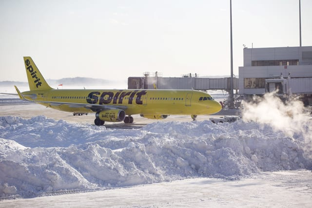 Spirit Airlines airplane prepares to drive around a large snow pile