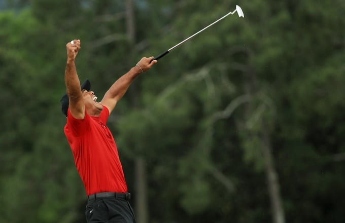 Tiger Woods of the United States celebrates after sinking his putt on the 18th green
