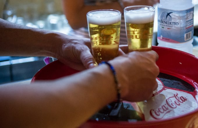 Waiter takes two beers to serve at the tables during the nightlife