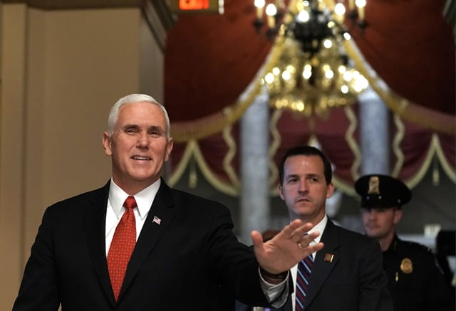 Mike Pence waves as he walks towards the House chamber