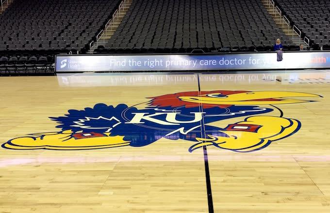 Kansas Jayhawks logo as it appears on a basketball court.