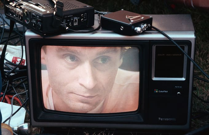 Ted Bundy's image on a television screen on the lawn of the Florida State Prison.