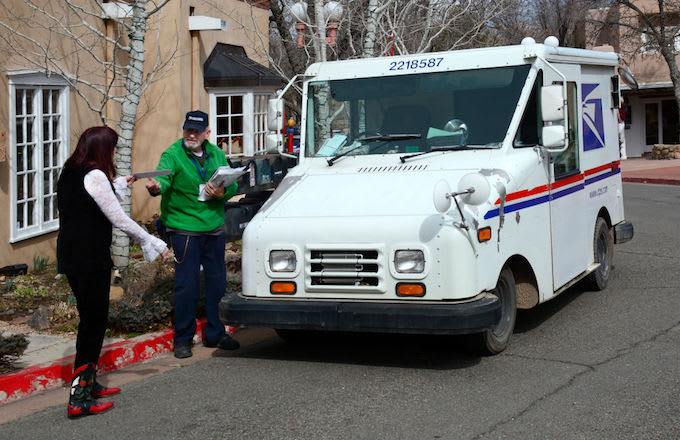 A USPS mailman delivering the mail.
