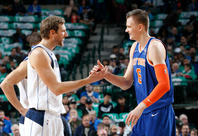 Dirk Nowitzki of the Dallas Mavericks greets Kristaps Porzingis
