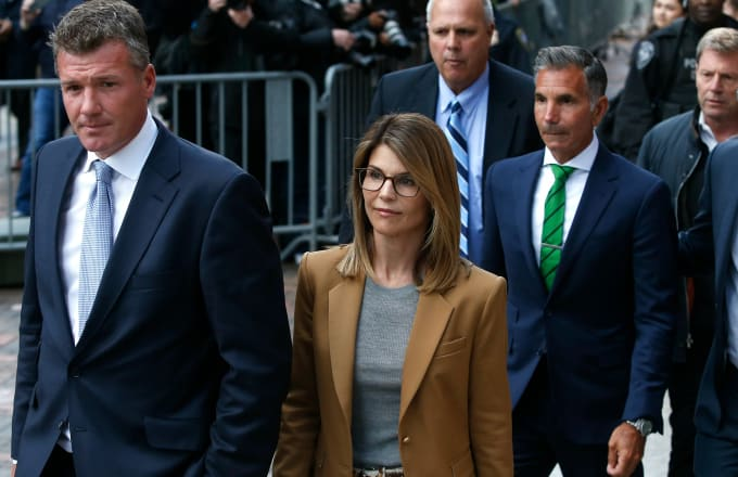 Lori Loughlin leaves as her husband Mossimo Giannulli, in green tie at right, follows