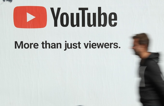 A man walks past a billboard advertisement for YouTube.