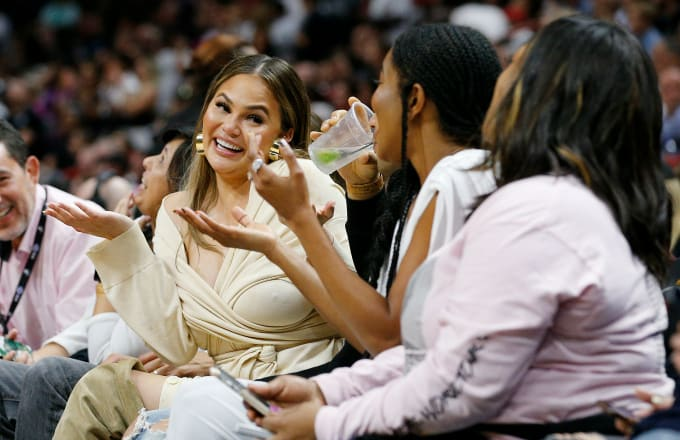 Chrissy Teigen reacts after Dwyane Wade crashed into her causing her
