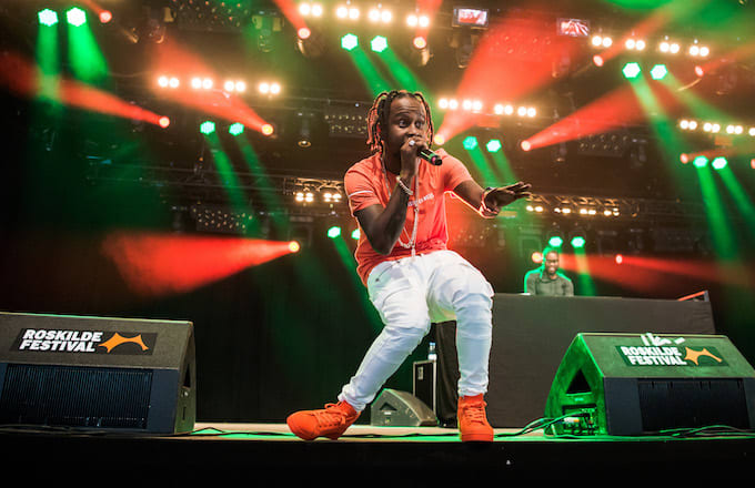 Popcaan performs on stage.