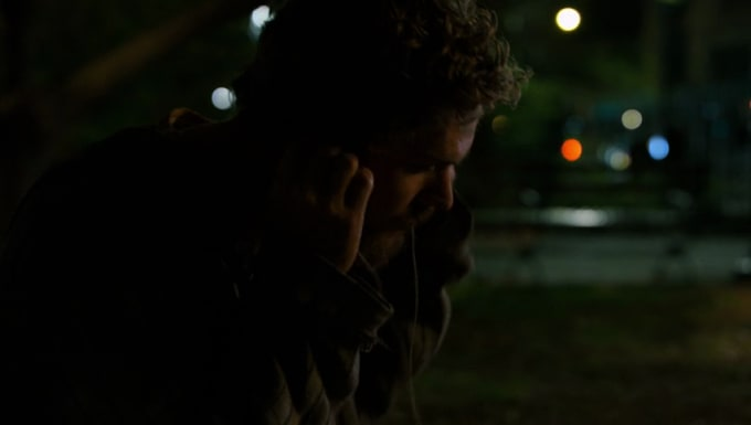 Danny Rand putting his headphones in
