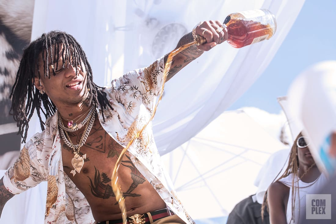 Swae Lee of Rae Sremmurd pouring out a bottle of Hennessy during his SremmLife Sundays performance.