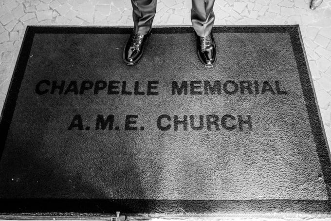 Dave Chappelle standing on the doorstep of Chappelle Memorial A.M.E. Church