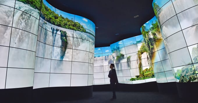 An attendee walks through LG's television display at CES 2018