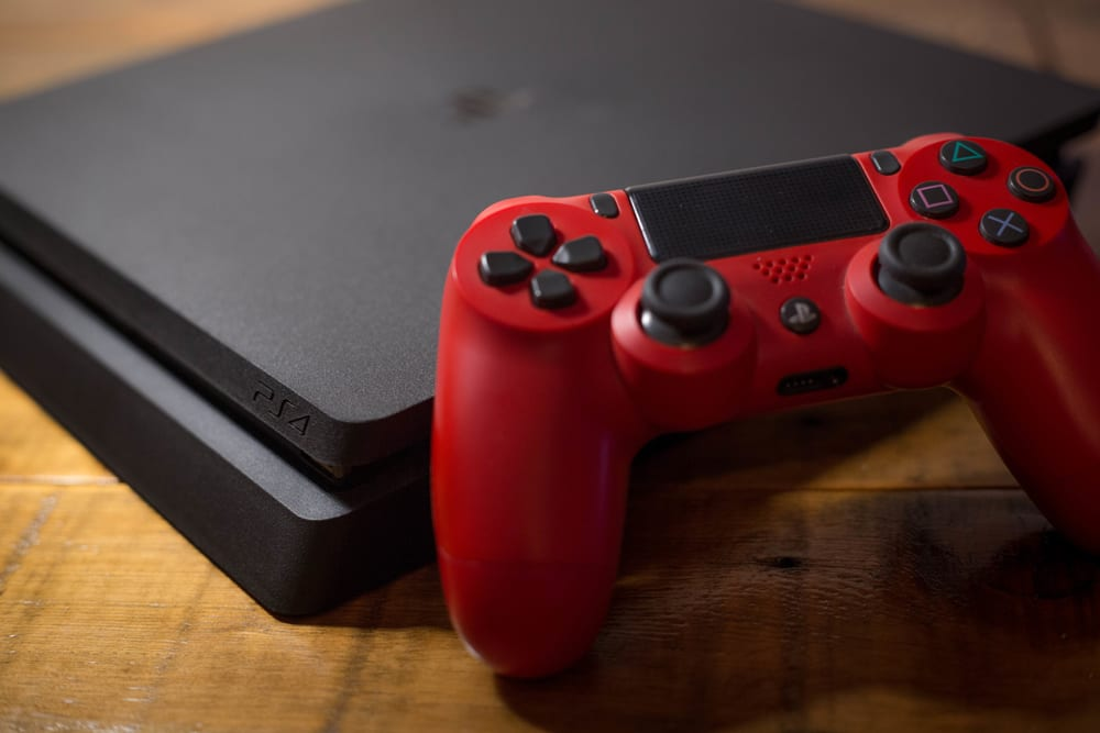 A Sony PlayStation 4 video game console with a red wireless controller