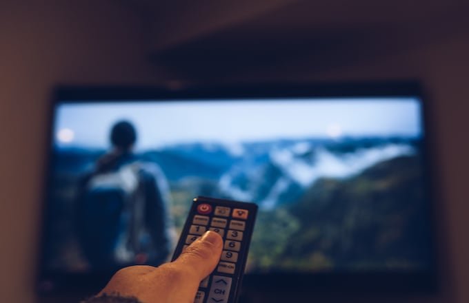 Image Of Hand Holding Remote Control In Front Of Television Set